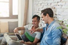 Zwei Männer, die Tablet-Computer-Internet am Café verwenden stockfotografie