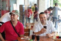 Zwei Männer an einem Cafétisch lächeln stockbild