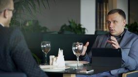 Zwei Männer haben MittagessenwarteBestellung bei der Sitzung im Café zuhause stock video footage