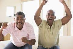 Zwei Männer im Wohnzimmer zujubelnd und lächelnd Stockfoto