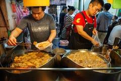 Zwei Männer kochen stinky Tofu am Straßenmarkt von Jiufen lizenzfreies stockfoto
