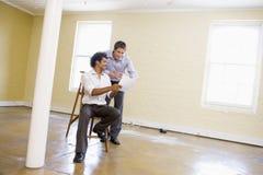 Zwei Männer mit Strichleiter im leeren Platz Stockbilder