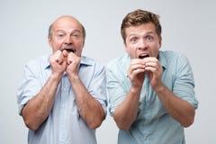 Zwei Männer reagieren auf plötzlichen Nachrichten, hält mouthes sich öffneten, Starren an der Kamera Vater und Sohn erhielten Nac lizenzfreies stockbild