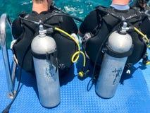 Zwei Männer sitzen in den schwarzen Taucheranzügen mit den Rohren und Metallsauerstoffflaschen, die zur Immersion bereit sind stockfotografie