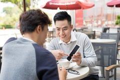 Zwei Männer teilen Nachrichten, Fotos, Video auf dem Smartphone lizenzfreies stockbild
