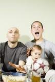 Zwei Männer und überwachendes Fernsehen des kleinen Jungen Lizenzfreies Stockfoto