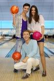 Zwei Männer und Mädchen halten Kugeln im Bowlingspielklumpen an Stockbilder