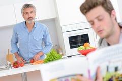 Zwei Männer in vorbereitendem Gemüse der Küche eine andere Lesung vom Rezeptbuch lizenzfreie stockfotos