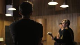 Zwei Männer, welche die E-Gitarren gesehen von der Seite spielen stock footage