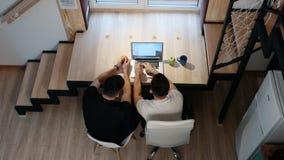 Zwei männliche Arbeiten über den Laptop, der durch das Innenministeriumkonzept der Tabelle sitzt Beschneidungspfad eingeschlossen stock video footage