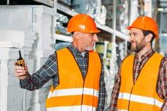 zwei männliche Arbeitskräfte in den Sicherheitswesten und Sturzhelme mit Funksprechgerät lizenzfreies stockbild
