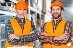 zwei männliche Arbeitskräfte in den Sicherheitswesten und Sturzhelme mit den gekreuzten Armen lizenzfreies stockbild