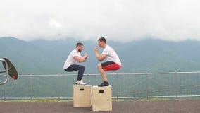 Zwei männliche athletische Freunde, die Kasten tun, springen Übung im Freien, die in den Bergen stock video