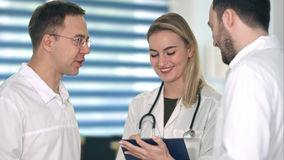 Zwei männliche Doktoren, die Diskussion während lächelnde Krankenschwester macht Anmerkungen in ihrem Klemmbrett haben Lizenzfreies Stockfoto
