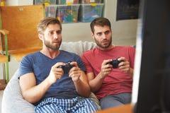 Zwei männliche Freunde in den Pyjamas, die zusammen Videospiel spielen Stockfotografie