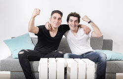 Zwei männliche Freunde, die auf einem grauen Sofa mit Kissen sitzen, umfassen bei der Herstellung von Gesten vom Sieg Stockfotografie