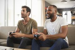 Zwei männliche Freunde, die auf Sofa In Lounge Playing Video-Spiel sitzen Lizenzfreie Stockfotos