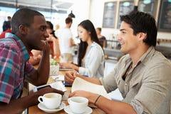 Zwei männliche Freunde, die in der beschäftigten Kaffeestube sich treffen Stockfotos