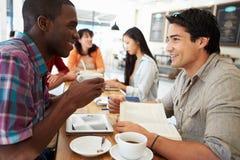 Zwei männliche Freunde, die in der beschäftigten Kaffeestube sich treffen Lizenzfreie Stockfotos