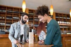 Zwei männliche Freunde, die Holzklötze beim Essen des Bieres betrachten Lizenzfreie Stockbilder