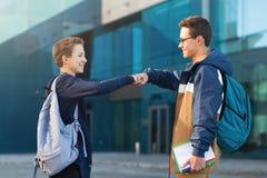 Zwei männliche Freunde, die oudoors, Jugendliche sich grüßen treffen lizenzfreie stockfotos