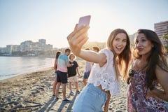Zwei männliche Freunde, die selfie auf Strand durch Smartphone nehmen Lizenzfreie Stockfotografie