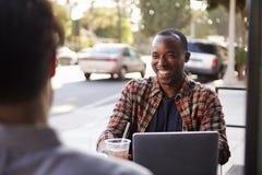 Zwei männliche Freunde mit kalten Getränken und Laptop außerhalb des Cafés Stockbild