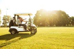 Zwei männliche Golfspieler, die in ein Golfmobil fahren lizenzfreie stockbilder