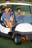 Zwei männliche Golfspieler, die in Golf-Buggy reiten lizenzfreie stockbilder