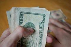 Zwei männliche Hände, die einen Satz Papierbanknoten halten (amerikanische Dollar, USD) und das Geld auf dem Holztisch, die geben Stockfotografie