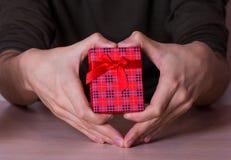 Zwei männliche Hände in Form Herz, das rote karierte Geschenkbox hält Stockfotografie