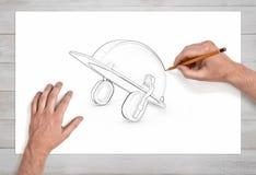 Zwei männliche Hände zeichnen eine Bleistiftskizze eines industriellen Schutzhelms mit Ohrenschützern auf Weißbuch Stockfotos