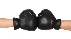 Zwei männliche Hände zusammen in den schwarzen Boxhandschuhen getrennt Lizenzfreie Stockfotos