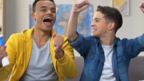 Zwei männliche Jugendliche, die Fußballspiel auf Fernsehen-, Singen und Schlaghorn aufpassen stock footage