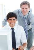 Zwei männliche Leitprogramme, die an einem Computer arbeiten stockfoto