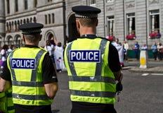 Zwei männliche Polizeibeamten in der Hallosichtjacke, welche die Menge zeugt Stockfotos