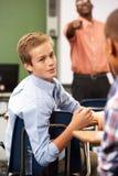 Zwei männliche Schüler, die in der Klasse sprechen lizenzfreie stockbilder