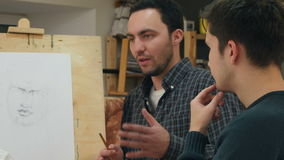 Zwei männliche Studenten, die Fragen über Zeichentechniken stellen stock video footage