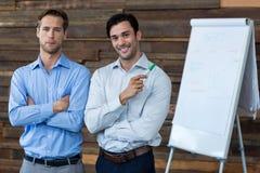 Zwei männliche Unternehmensleiter in einer Sitzung, die vor einer Flip-Chart steht lizenzfreies stockfoto