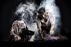 Zwei männliche Zombies, die auf ihre Knie, auf schwarzem rauchigem Hintergrund kriechen stockfoto