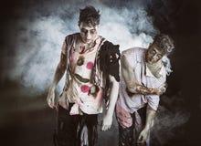 Zwei männliche Zombies, die auf schwarzem rauchigem Hintergrund stehen Lizenzfreie Stockfotografie