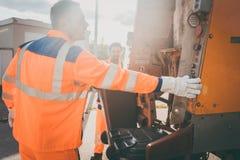 Zwei Müllabfuhrarbeitskräfte, die Abfall in überschüssigen LKW laden Stockfotografie