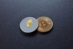 Zwei Münzen Schlüsselwährung ETH, BTC auf einem schwarzen konkreten Hintergrund Geschäfts-, Finanz- und Technologiekonzept Lizenzfreies Stockbild