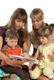 Zwei Mütter lasen Bücher zu ihren Kindern Stockbilder