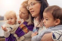 Zwei Mütter mit Babys in der Babytrageverzerrung stockbilder