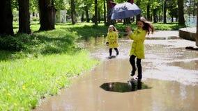 Zwei M?dchenspielen und -betrieb durch Pf?tzen im Park stock footage