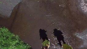 Zwei M?dchenspielen und -betrieb durch Pf?tzen im Park stock video