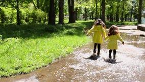 Zwei M?dchenspielen und -betrieb durch Pf?tzen im Park stock video footage