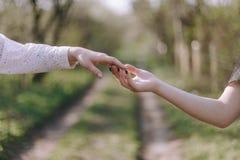 Zwei m?nnliche H?nde, die in Richtung zu einander, fast ber?hrend mit den Fingern erreichen und beleuchten Funken im Galaxiehinte lizenzfreie stockfotografie