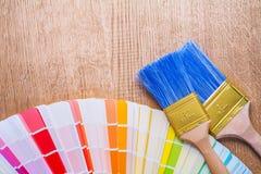 Zwei Malerpinsel auf Farbpalette und hölzernem Brett Stockbild